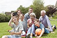 Boy taking selfie of happy extended family in garden - RBF004761