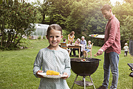 Smiling girl holding plate with corn cob on a family barbecue - RBF004773