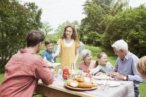 Happy extended family dining in garden - RBF004776