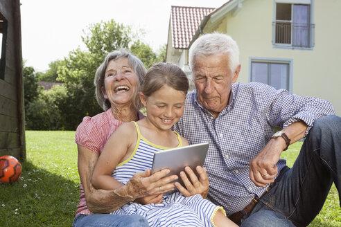 Grandparents and granddaughter in garden using digital tablet - RBF004800
