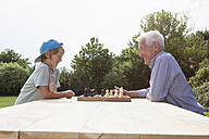 Grandfather and grandson playing chess in garden - RBF004803