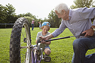 Grandfather inflating grandson's bicycle in garden - RBF004806