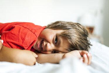 Portrait of smiling little boy lying on bed - VABF000718