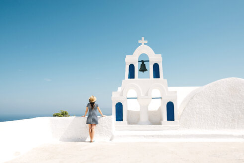 Greece, Santorini, Oia, back view of woman standing next to bell tower looking to the sea - GEMF000930
