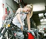 Young woman repairing motorbike - MADF001032