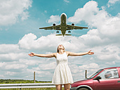 Car and plane behind young woman stretching out her arms - MADF001053