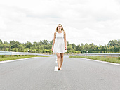 Young woman in white dress walking barefoot on country road - MADF001056