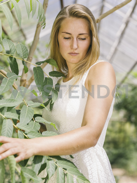 Blond young woman in white dress in greenhouse - MADF001059