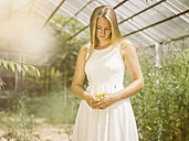 Blond young woman in white dress standing in greenhouse holding flowers - MADF001062