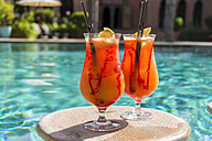 Fruity cocktails floating on swimming pool - JUNF000539