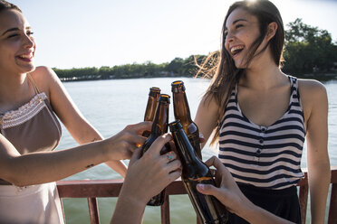Friends relaxing together at sunlight toasting with beer bottles - ABZF000877