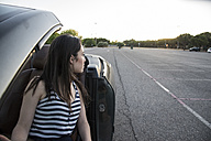 Young woman sitting in convertible watching something - ABZF000883