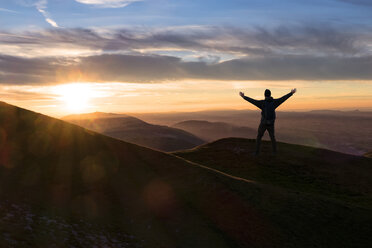 Italy, Umbria, Monte Acuto, Sunset over Umbrian Apennines, hiker with raising arms - LOMF000315
