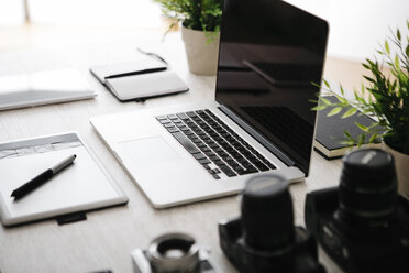 Desk of photographer with laptop, cameras, tablet and graphics tablet - JRFF000779