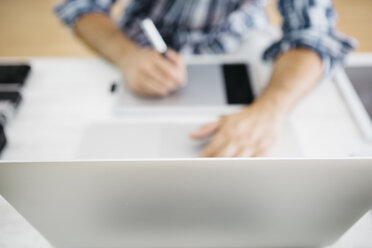 Man working at desk with laptop and graphic tablets, partial view - JRFF000782