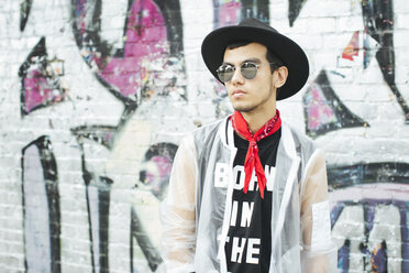 Fashionable young man with hat and sunglasses wearing translucent rainjacket - JUBF000168