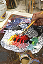 Artist using paintbrush and artist's palette, partial view - JTF000765