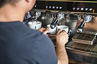 Man preparing coffee at coffee machine - DIGF000812