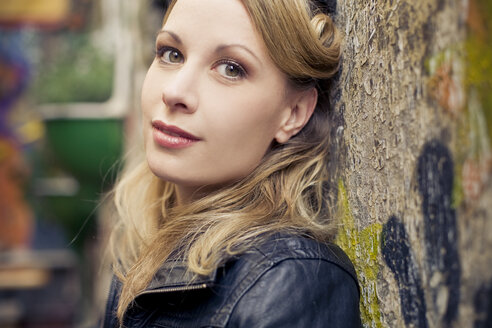 Portrait of blond woman leaning against wall - NGF000360