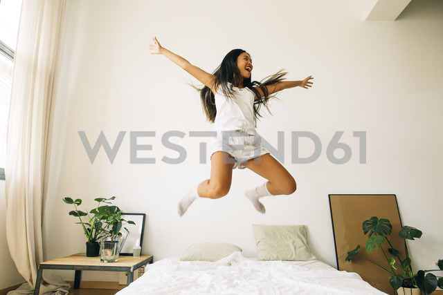 Exuberant young woman jumping on bed - EBSF001579