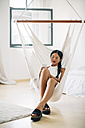Young woman sitting in hammock using cell phone - EBSF001585
