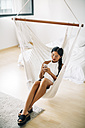 Young woman sitting in hammock using cell phone - EBSF001591