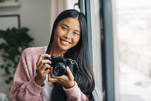 Portrait of smiling young woman with camera looking near window - EBSF001618