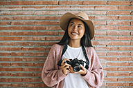 Portrait of smiling young woman with camera in front of brick wall - EBSF001621