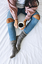 Woman with cup of coffee relaxing on bed, partial view - EBSF001624