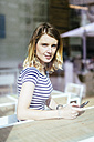 Portrait of young woman in a coffee shop looking through window - GIOF001317