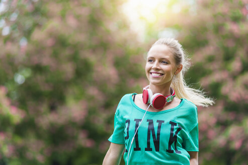 Portrait of happy blond woman with headphones in a park - DIGF000825