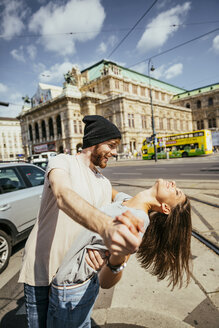 Austria, Vienna, happy young couple dancing Viennese waltz in front of state opera - AIF000359