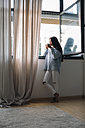 Young woman with cup of coffee standing in front of open window - EBSF001629