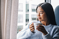 Young woman with cup of coffee standing in front of open window - EBSF001632