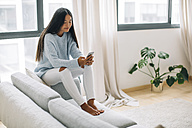 Young woman sitting on couch in the living room using smartphone - EBSF001635
