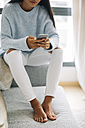 Young woman sitting on couch using smartphone, partial view - EBSF001638