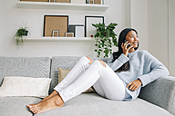 Young woman sitting on couch at home telephoning with cell phone - EBSF001641