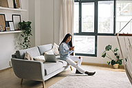Young woman sitting on couch at home looking at smartphone - EBSF001650