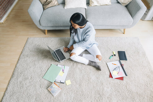 Young woman sitting on floor in the living room using laptop - EBSF001656