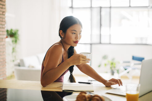 Woman with cup of coffee working with laptop at home - EBSF001666
