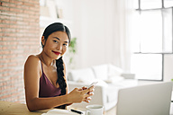 Portrait of smiling woman with cell phone at home - EBSF001669