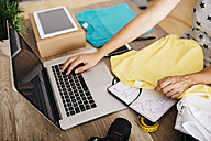 Woman with garment using laptop on desk - JRFF000796