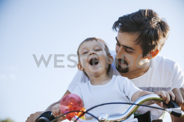 Laughing little boy on bicycle tour with his father - ZEDF000256 - Zeljko Dangubic/Westend61