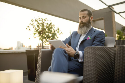 Bearded businessman sitting on roof terrace looking at tablet - JASF001026