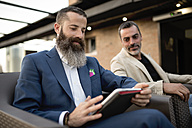 Bearded businessman sitting on roof terrace usinf tablet while another man watching him - JASF001032