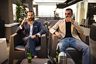 Two men sitting side by side on roof terrace smoking cigarettes - JASF001041