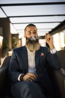 Bearded man sitting on roof terrace in the evening smoking cigarette - JASF001044