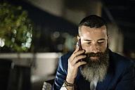 Portrait of bearded man telephoning  on a terrace - JASF001047