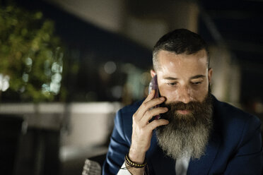 Portrait of bearded man telephoning  on a terrace - JASF001047