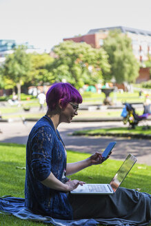 Young woman with dyed hair sitting on a meadow using laptop and cell phone - BOYF000468
